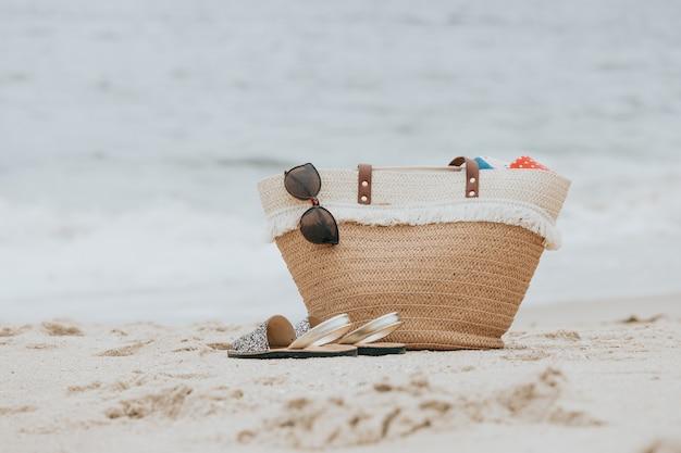 Accessori da spiaggia alla moda sulla riva del mare sabbioso con borsa estiva, sandali e occhiali da sole.