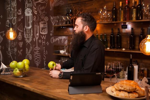 Elegante barista barbuto in una camicia sullo sfondo del bancone del bar. pub alla moda.