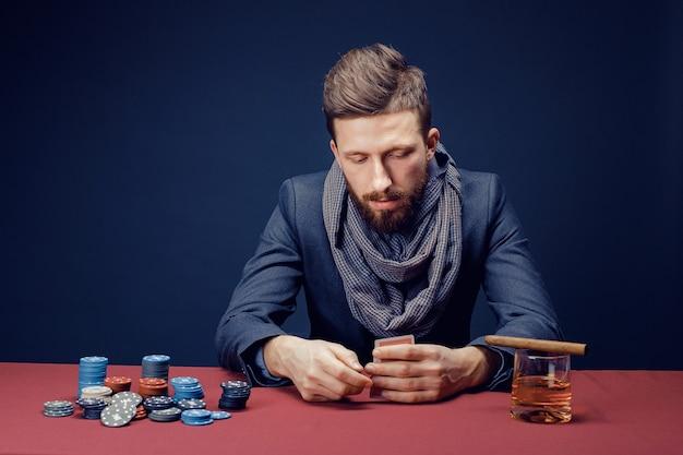 Elegante uomo barbuto in vestito e sciarpa che giocano nel casinò scuro