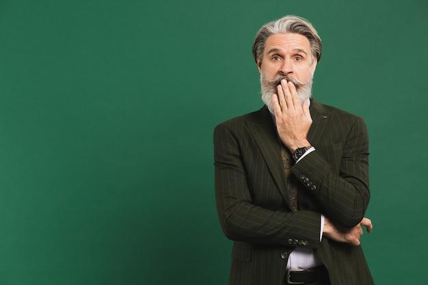 Elegante uomo di mezza età con la barba in tuta chiude la bocca con la mano su una parete verde