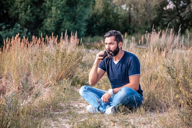 Elegante vaper barbuto che gode di un dispositivo elettronico per il fumo nel bosco
