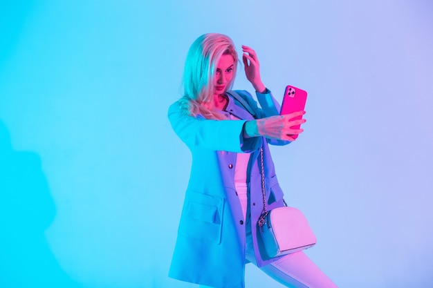 Elegante bella donna bionda in un tailleur alla moda con una giacca e una borsa si fotografa su uno smartphone in studio contro una luce rosa al neon. selfie creativo