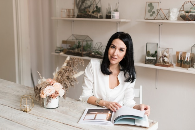Elegante bella bruna in una camicia bianca e con un orologio che legge una rivista al tavolo
