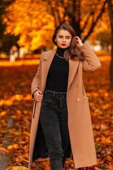 Elegante bella ragazza d'affari con labbra rosse in un cappotto beige alla moda con un maglione e jeans neri cammina in un parco con fogliame autunnale colorato
