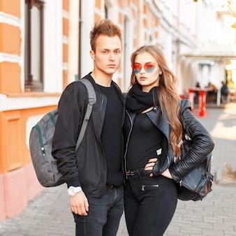 Elegante bella coppia in abiti alla moda con borse che viaggiano insieme