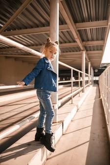 Una bella ragazza alla moda di circa sette anni con una giacca di jeans cammina per strada