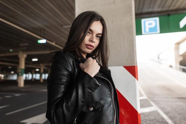 Bella ragazza alla moda in abiti neri alla moda con una giacca di pelle cammina in città