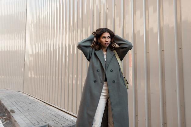 Elegante bella ragazza con i capelli ricci in un cappotto lungo verde alla moda con una borsa alla moda passeggiate in città vicino a un muro di metallo. stile primavera casual femminile