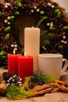 Elegante bella composizione di capodanno di coni di abete rosso e candele