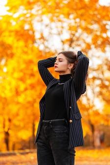 Elegante bella ragazza d'affari di successo in un abito nero alla moda con un maglione vintage e blazer cammina all'aperto su uno sfondo di fogliame autunnale al tramonto