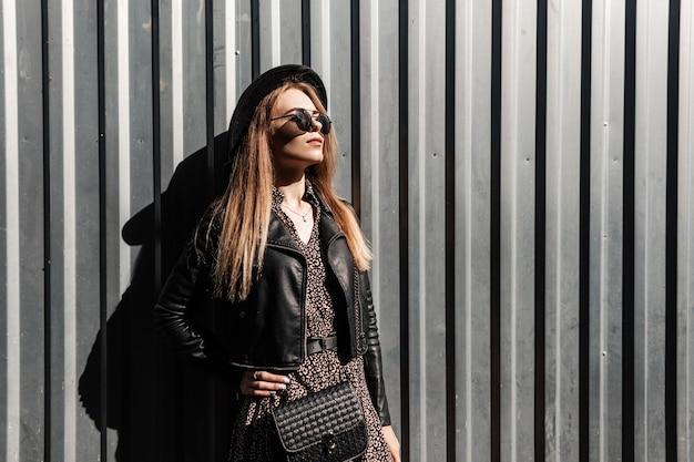 Bella donna alla moda in abiti alla moda con occhiali da sole e un cappello in un abito vintage. giacca di pelle con una borsetta si trova vicino a una parete di metallo con tempo soleggiato