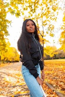 Elegante bella ragazza nera in abiti alla moda con una giacca, jeans e una borsa bianca in natura con fogliame autunnale giallo brillante