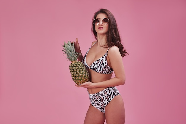 Elegante bella ragazza in bikini si leva in piedi e in posa