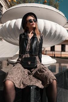 Elegante modello di bella ragazza in abito alla moda con una giacca di pelle e una borsa vintage si siede per strada in una giornata di sole. stile e bellezza estivi femminili