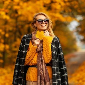 Elegante bella ragazza in abiti estivi alla moda con un cappello, occhiali e un top a righe alla moda si trova vicino a un edificio moderno in città