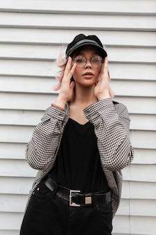 Elegante bella ragazza con gli occhiali in un cappello alla moda con una camicia a scacchi casual si trova vicino a uno sfondo di casa in legno