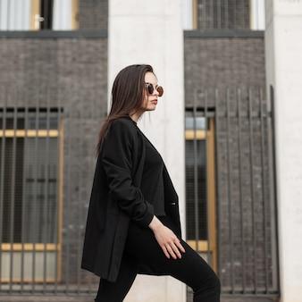 Elegante bella ragazza con occhiali da sole in giacca nera e pantaloni cammina per strada