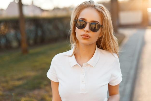 Elegante bella giovane donna hipster in occhiali da sole alla moda in una t-shirt polo bianca è in piedi sulla strada di un tramonto estivo. bionda ragazza carina moda.