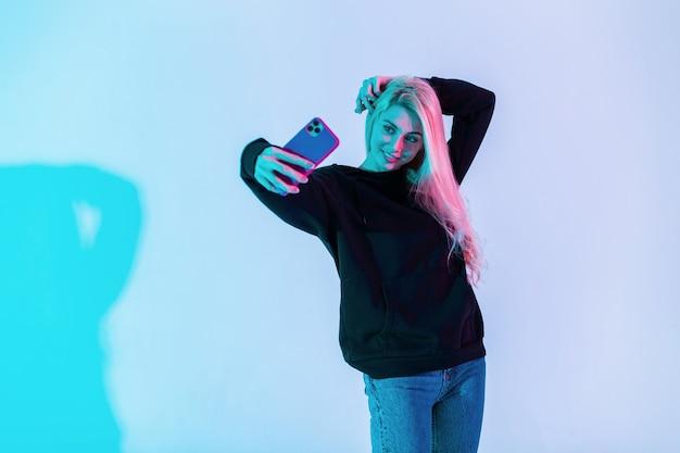 Elegante bella giovane donna in una felpa con cappuccio nera alla moda con jeans fa un selfie su un telefono cellulare in studio su uno sfondo rosa neon multicolore. immagine creativa