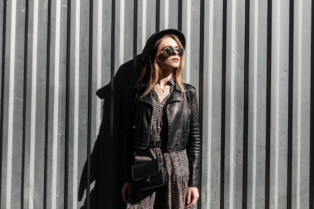 Elegante bella giovane donna in una giacca di pelle nera alla moda con un vestito e una borsa in occhiali da sole vicino a un muro di metallo sulla strada
