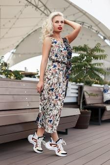Elegante bella giovane donna in un vestito alla moda con un motivo e scarpe da ginnastica in città