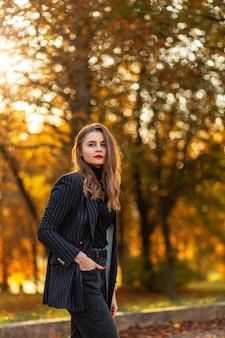 Elegante bella giovane donna in abiti eleganti alla moda con un blazer nero, un maglione e jeans che camminano in un parco con fogliame autunnale giallo brillante al tramonto