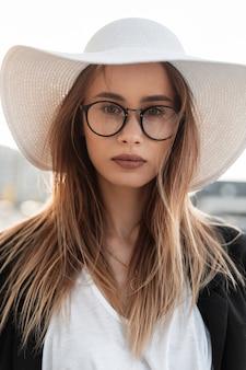 Elegante bella giovane donna con gli occhiali in un cappello alla moda con una giacca nera e una maglietta bianca per strada. giovane imprenditrice all'aperto. collezione abbigliamento donna estiva giovanile