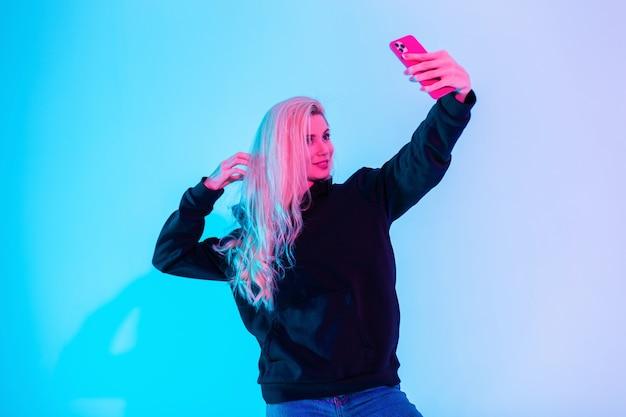 La bella giovane donna alla moda fa il selfie sullo smart phone con le luci al neon rosa in studio