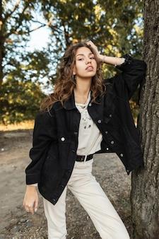Elegante bella giovane donna con capelli ricci in una giacca di jeans nera alla moda e pullover lavorato a maglia vicino a un albero su una natura rurale in un parco
