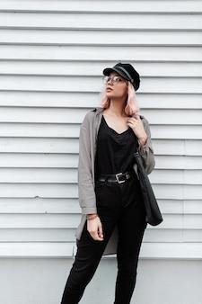 Elegante bella ragazza giovane in abiti casual alla moda con una camicia, maglietta nera e jeans con occhiali e un berretto si trova vicino a una parete di legno
