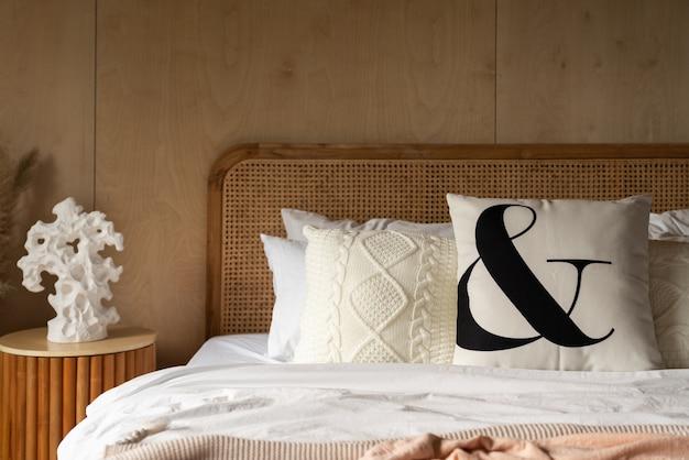 Elegante angolo della camera da letto con testiera in rattan e soffice cuscino decorato