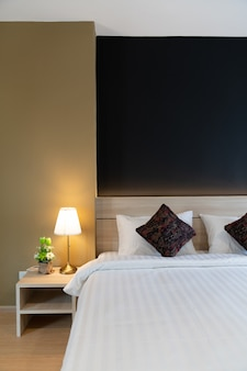 Elegante angolo camera da letto con soffice testiera in legno con morbidi cuscini e pareti dipinte di blu navy e giallo