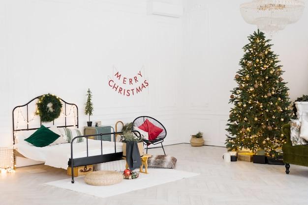 Design elegante della camera da letto con decorazioni natalizie in stile scandinavo o vintage con un albero di natale