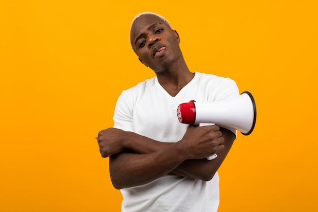 Uomo americano bello nero alla moda in maglietta bianca che tiene un megafono su fondo arancio isolato