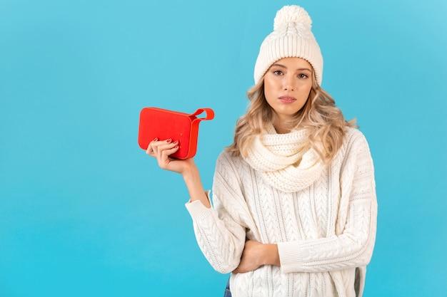 Bella giovane donna bionda alla moda che tiene altoparlante senza fili che ascolta la musica che indossa maglione bianco e cappello lavorato a maglia stile invernale in posa isolato sulla parete blu