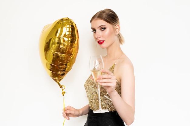 Elegante ragazza bionda in canotta di paillettes e gonna nera con palloncino a forma di cuore e tostatura con flute di champagne alla festa