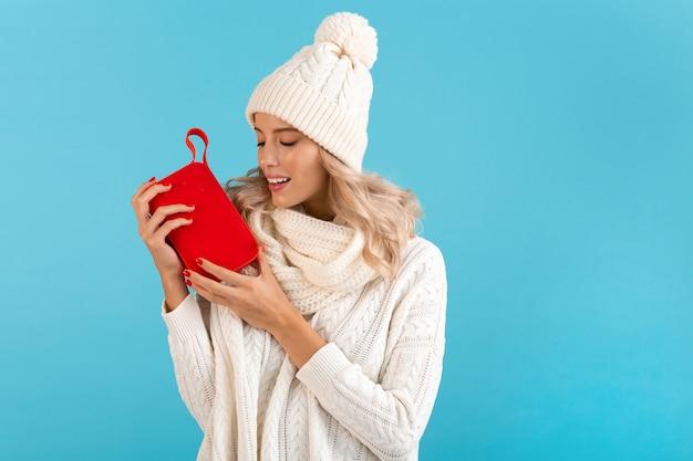 Bella giovane donna sorridente bionda alla moda che tiene altoparlante senza fili che ascolta la musica maglione bianco da portare felice e cappello lavorato a maglia che posa sull'azzurro