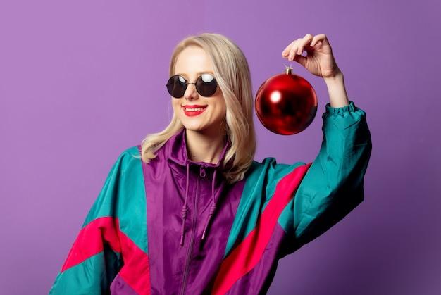 Elegante bionda in giacca a vento anni '80 e occhiali da sole roud tiene la pallina di natale sul muro viola