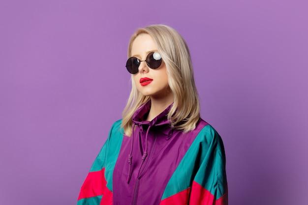 Elegante bionda anni '80 in giacca a vento e occhiali da sole rotondi sul muro viola