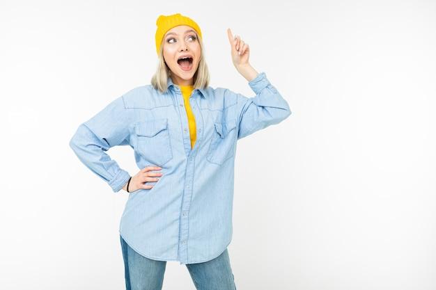 La ragazza bionda alla moda mostra un dito sull'idea su un fondo bianco isolato