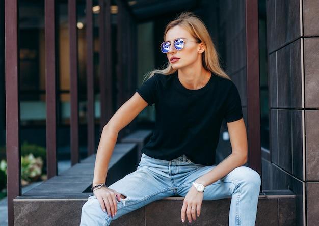 Elegante ragazza bionda che indossa t-shirt nera e occhiali in posa contro la strada
