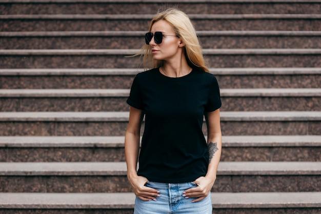Ragazza bionda alla moda che indossa maglietta nera e vetri che posano contro la via