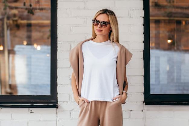 Elegante ragazza bionda che indossa t-shirt bianca e occhiali
