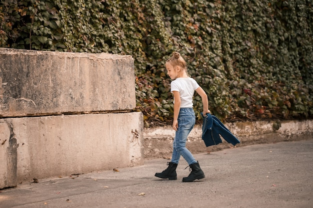 Elegante bambina bionda in jeans e una maglietta bianca cammina per strada. bambina di 7 anni modella piccola, bellissima bambina