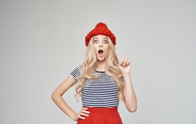 Elegante bionda in una maglietta a righe e gesti di cappello lavorato a maglia con le mani copia spazio