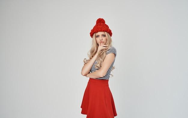 Elegante bionda in una maglietta a righe e gesti di cappello lavorato a maglia con le mani copia spazio.