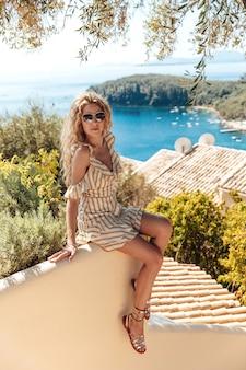 Donna bionda alla moda che gode delle vacanze estive vicino al mare