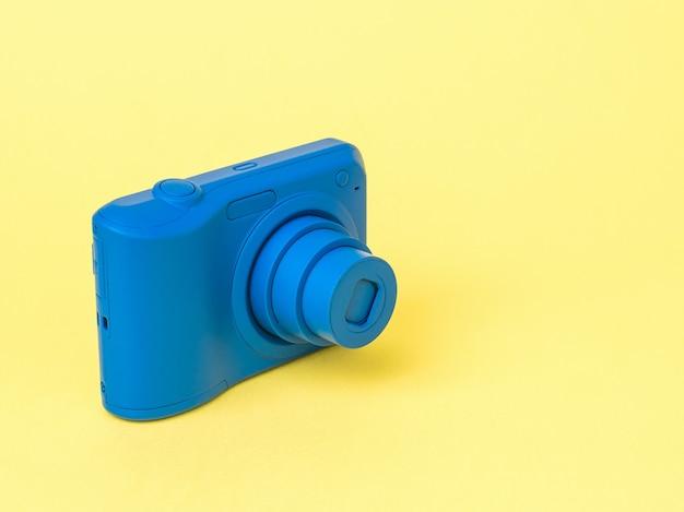 Elegante fotocamera blu con obiettivo esteso su una superficie gialla. attrezzatura elegante per riprese di foto e video.