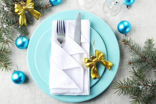 Elegante tavola di natale blu e bianca su tovaglia grigia