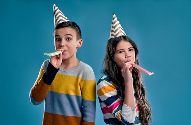 Ragazzo alla moda e ragazza carina con tappi per le vacanze, coni in testa che soffia fischietti, festeggia un compleanno isolato su un blu.
